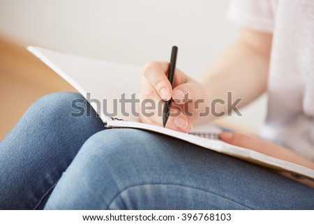 Close up lifestyle image of pretty young teenage girl sitting on her floor and making notes to her diary. Bright colors. - stock photo