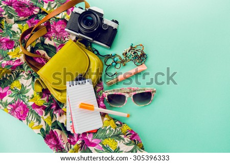 Close up lifestyle photo of hipster student accessories . Still life of random objects of modern girl / woman. Leather bag, camera, Sunglasses, paper notepad, Aerial view. Sunny summer colors. - stock photo