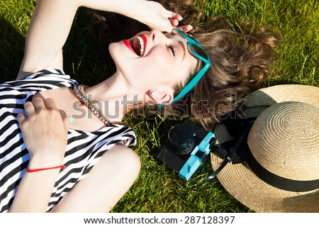 Close up lifestyle portrait of cheerful brunette hipster girl going crazy making funny face and showing her tongue.Laying on the ground and laughing.Bright colors,urban street background.accessories - stock photo