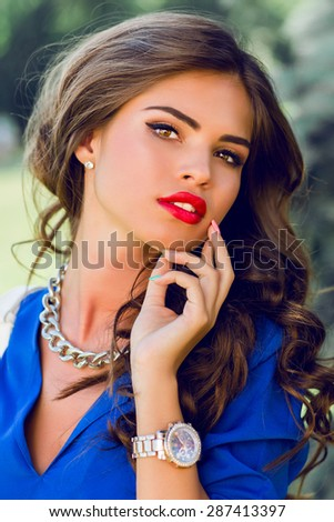 Close up lifestyle portrait of stunning brunette woman in  summer  casual outfit. Beautiful lady posing in the green summer park  lawn background . - stock photo