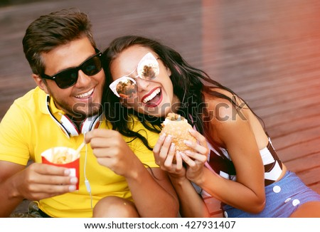 Close up lifestyle portrait of two happy peoples,couple in love,laughing and having fun  .Pretty young girl in jeans jacket and her handsome boyfriend dating.Feeding each other, Romantic mood. - stock photo