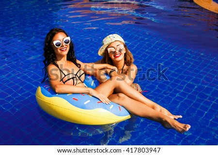 Close up lifestyle portrait of two pretty fresh young best friends girls, having fun. Relaxing on the pool at hot summer days, Wearing sunglasses. make photos, crazy emotions, rubber ring, donut - stock photo