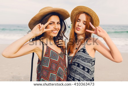 Close up lifestyle portrait of two pretty fresh  young  best friends girls,show signs  and have fun. Wearing  sunglasses and make photos, showing  tongue, crazy emotions. - stock photo