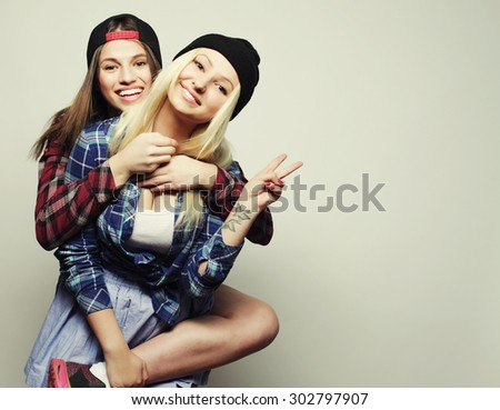 Close up lifestyle portrait of two pretty teen girlfriends smiling and having fun, wearing hipster clothes and hats, positive mood. - stock photo