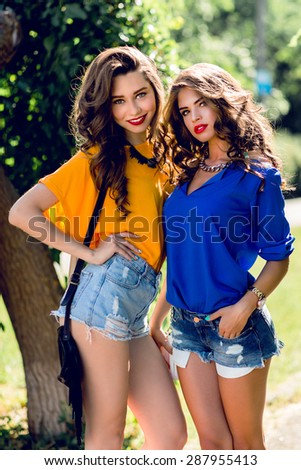 Close up lifestyle portrait of two   pretty women  hugs and smiling. Girlfriends having fun and l walking in the sunny summer  park. Wearing casual outfit . - stock photo
