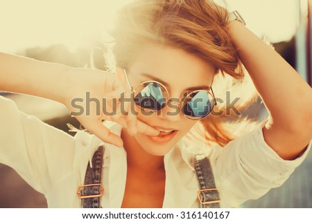 Close-up Lifestyle soft portrait of young amazing smiling positive girl, long blonde fluffy hairs, fresh natural make up, stylish clothes and accessorizes , pure beauty.Trendy glasses  - stock photo