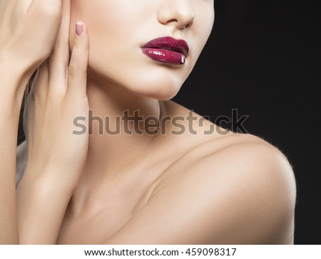 Close-up lips and shoulders of caucasian brunette woman with wet red lipstick and arms touching face. Isolated on black background. - stock photo