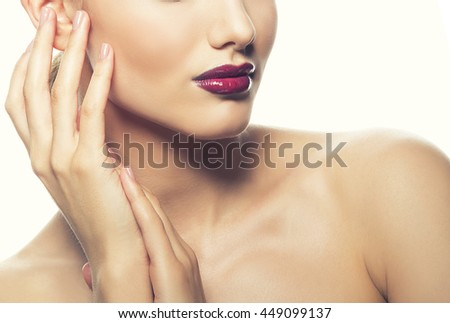 Close-up lips and shoulders of young caucasian brunette woman with red glossy lips, intensive make-up, perfect skin and blue eyes isolated on white touch her skin. Studio portrait. Toned - stock photo