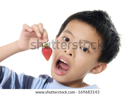 Close up little boy eats strawberries  - stock photo