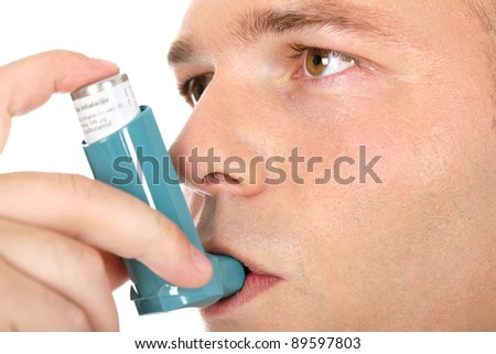 Close up look of a man with pump in his mouth, against asthma - stock photo