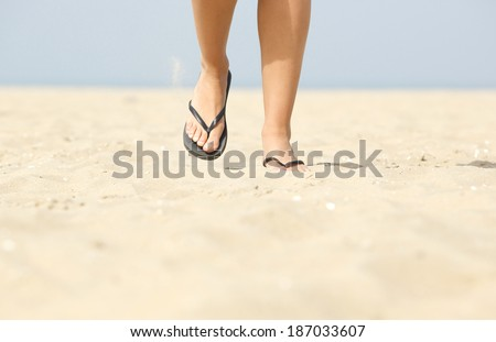 Close up low angle front view of woman walking on beach with flip flops - stock photo