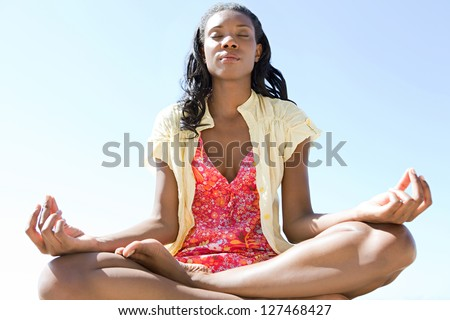 Close up low view of a healthy and attractive african american woman in a yoga position meditating against a bright blue sky on a sunny day. - stock photo