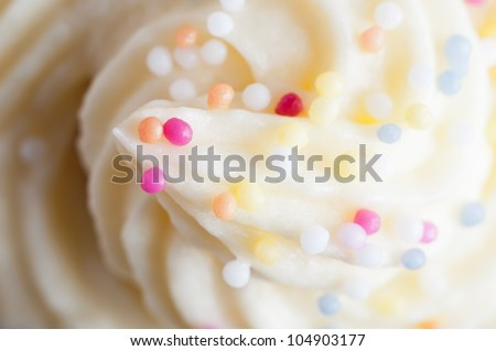 Close up (macro) of a cake topping made from swirled buttercream icing and colourful decorative sprinkles. - stock photo