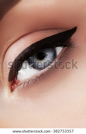 Close-up macro of beautiful female eye with perfect shape eyebrows. Clean skin, fashion naturel make-up. Good vision. Classic fashion eye liner makeup. Black eyeliner and brown eyeshadows  - stock photo