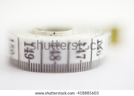 Close up macro view of a curved measuring tape. Measuring tape of the tailor. Closeup view of white measuring tape. Selective focus on a number distance. - stock photo