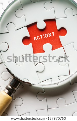 """Close up Magnifying glass searching missing puzzle peace """"action"""" - stock photo"""
