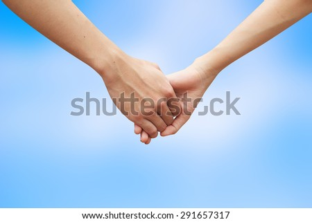 close up male and female hands holding together on blurred blue sky backgrounds. passion in love concept. - stock photo