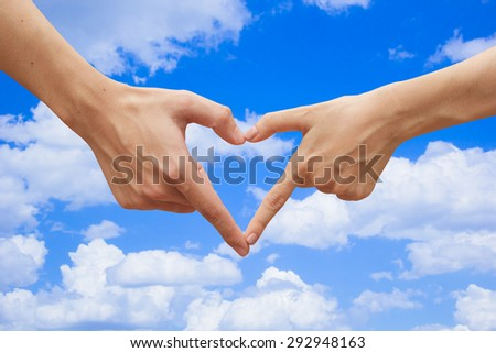 close up male and female hands making heart on blurred blue sky backgrounds . passion in love concept ,soft focused - stock photo