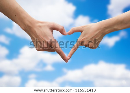 close up male and female hands making heart on blurred bright sunny sky backgrounds . passion in love concept ,soft focused.picture use for work about decorate,design,card,valentines and etc. - stock photo