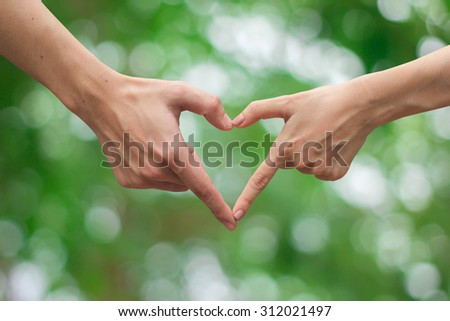 close up male and female hands making heart on blurred nature backgrounds . passion in love concept ,soft focused.picture use for work about decorate,design,wedding,card,valentines and etc. - stock photo