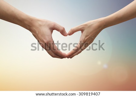 close up male and female hands making heart shape on blurred vintage colors backgrounds . passion in love concept ,soft focused.useful for work about decorate,design,wedding,card,valentines and etc. - stock photo