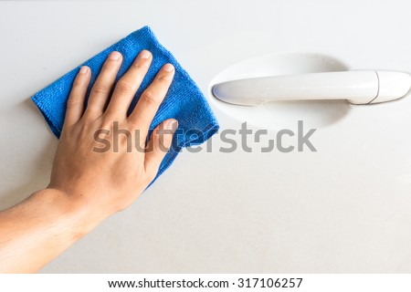 Close up male hand with blue microfiber cloth cleaning the car - stock photo