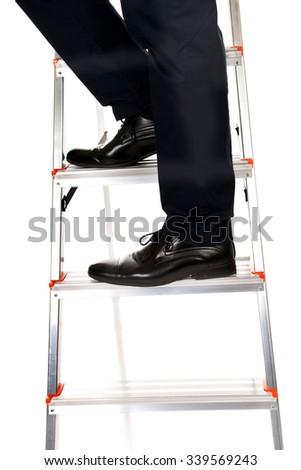 Close up male legs climbing ladder. - stock photo