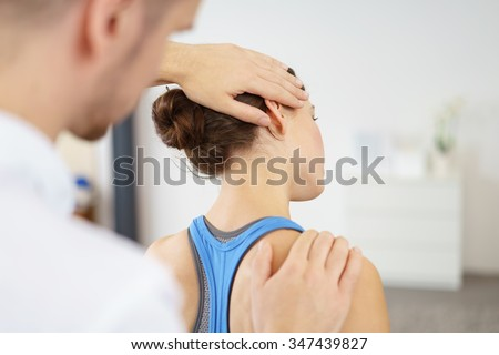 Close up Male Physical Therapist Stretching the Injured Neck of a Female Patient Slowly. - stock photo