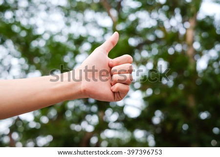close up man hand gesture and showing thumb up on blur green nature bokeh background:human sign/symbols concept:selective focus. - stock photo