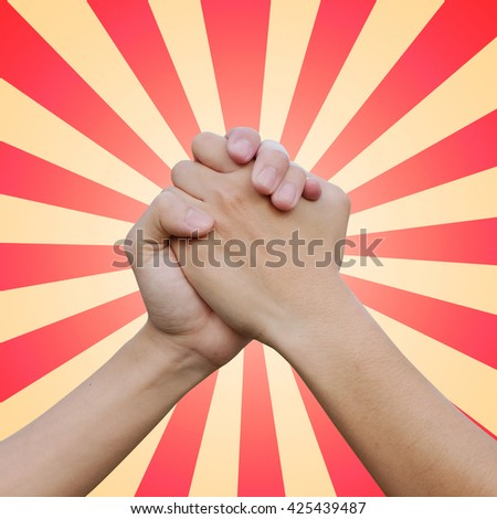 close up man handshake on sunburst color background with ray light:man hands shake for confident,success,victory,assurance concept:trust and love of humanity conceptual idea.square frame picture - stock photo