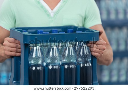 Close up Man Holding One Dozen of Bottled Water with No Label in a Blue Plastic Case. - stock photo