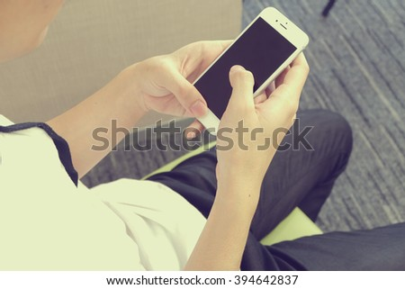 close up man's hand holding mobile phone device:focus on boy work/play/read/call/text/type on smart phone concept:human people and innovation technology conception.addiction of smartphone symptoms. - stock photo