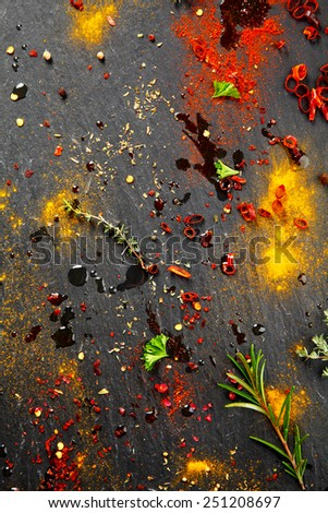 Close up Messy Black Table with Assorted Colored Rub and Marinade Spices - stock photo