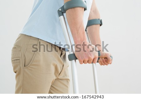 Close-up mid section of a man with crutches standing against white background - stock photo