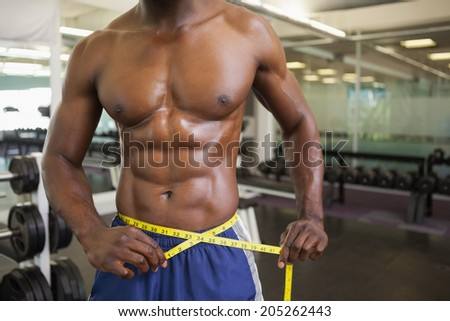Close-up mid section of a muscular man measuring waist in gym - stock photo