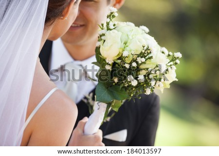 Close-up mid section of a young newlywed couple with bouquet in the park - stock photo