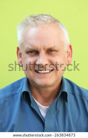 Close up Middle Age Man with Short White Hair Smiling at the Camera, Isolated on Yellow Green Background. - stock photo
