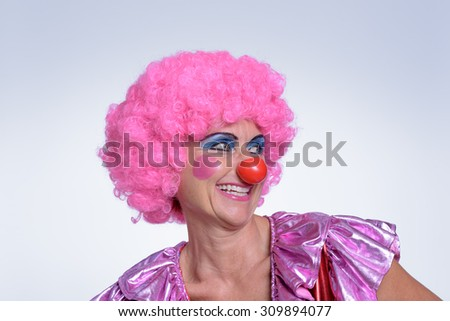 Close up Middle Aged Female Clown with Pink Wig, Smiling Into the Distance Against White Background. - stock photo