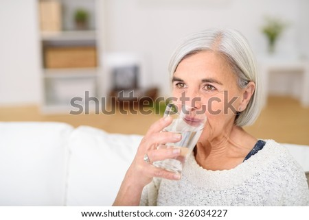 Close up Middle Aged Woman Drinking a Glass of Water at the Living Room and Looking Into the Distance. - stock photo