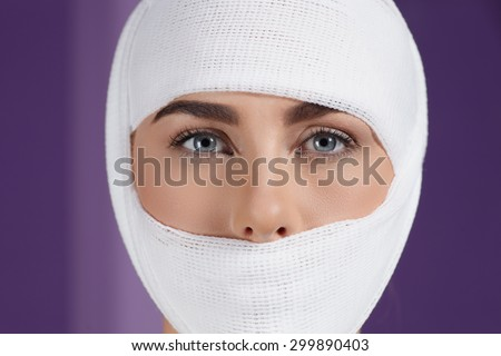 Close up models face in medical bandage after bueauty surgery - stock photo
