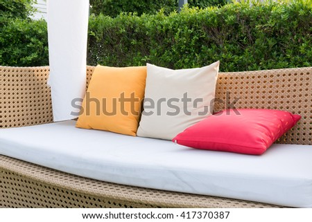 Close up modern sofa  wicker and color pillows in the garden. - stock photo
