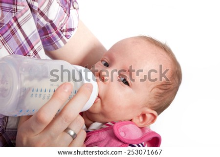 Close up Mother Feeding her Cute Baby with Milk in a Battle. Captured with White Background. - stock photo