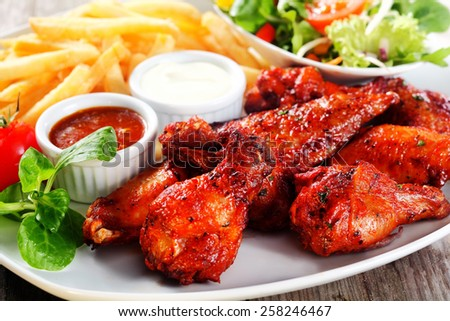 Close up Mouth Watering Flavored Fried Chicken on Plate with Homemade Sauces, Paired with Potato Fries and Vegetables - stock photo