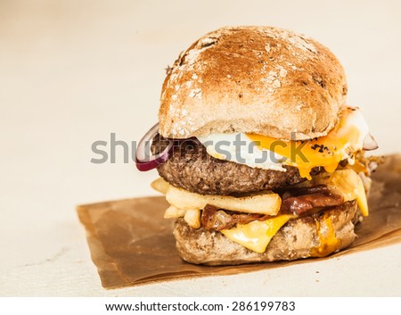 Close up Mouth Watering Homemade Burger with Patty, Cheese, Onion Rings and Fries on Top of a Brown Paper, Isolated on beige Background. - stock photo