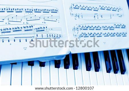 Close-up musical notes sheet and piano - stock photo