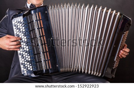Close-up musician playing the accordion against a black background - stock photo