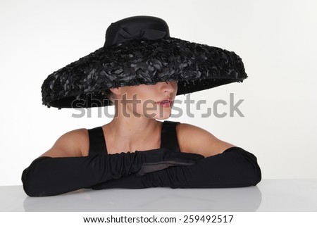 Close up Mysterious Woman Wearing Elegant Black Feathery Hat and Long Gloves Leaning on the Table, Isolated on White Table. - stock photo