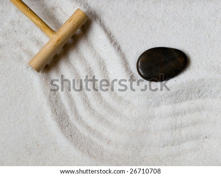 Close-up of a a Japanese zen garden with a wooden rake and a black stone. - stock photo