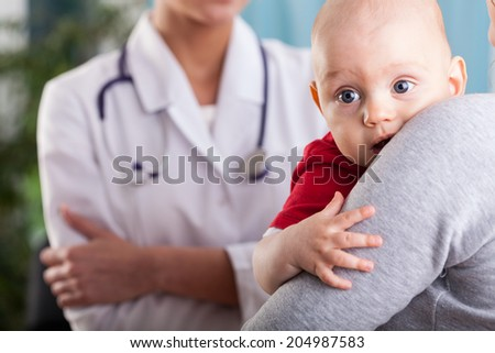 Close-up of a baby boy in the arms of mother at doctor's office - stock photo