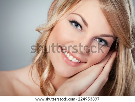 Close-up of a beautiful blond woman with a perfect smile. - stock photo